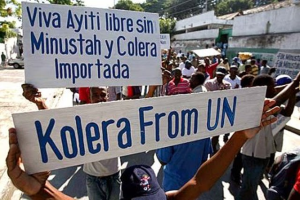 """Protestors in Port-au-Prince carry signs reading """"Long live a free Haiti without MINUSTAH and imported cholera"""" and """"Cholera from the UN"""" http://zenpolitikayiti.blogspot.com/2014_07_01_archive.html"""